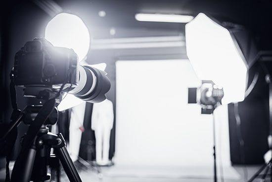 Large photo studio with professional lighting equipment and a camera on a tripod.