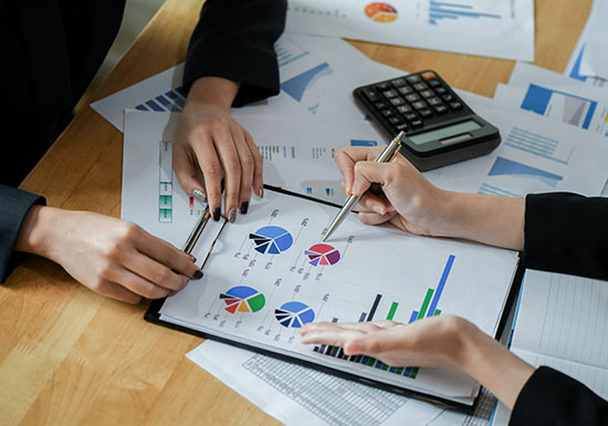 Female accountant team is analyzing the data to present the client.They use the pen at the data graphs and consult the job.